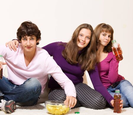 crisps: Hungry friends with crisprs and drinks in bottles Stock Photo