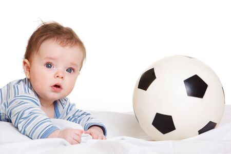 surprised baby: Baby lying beside soccer ball