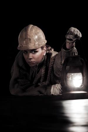 Beautiful young woman in hardhat with oil stove  photo