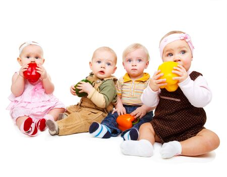 Four cute babies group holding large peppers in hands Stock Photo - 8978401