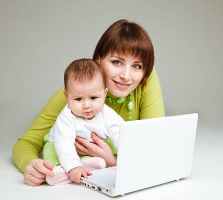 Mother working at the laptop, baby beside her photo
