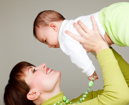 Woman holding baby in hands and raising up high photo