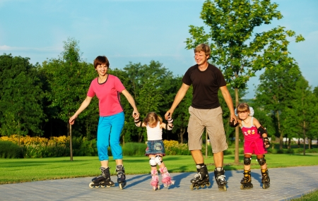 family in park: A happy family skating in a summer park Stock Photo