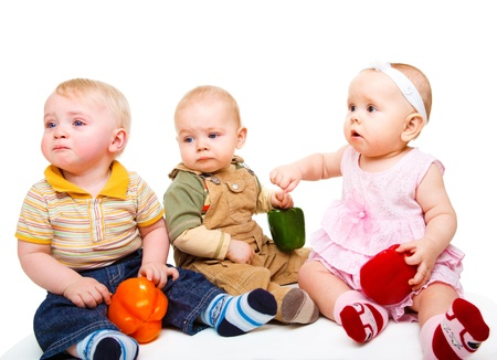 Three surprised baby friends holding ripe peppers photo