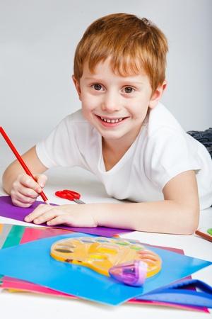 Joyful elementary-aged boy drawing, over gray photo