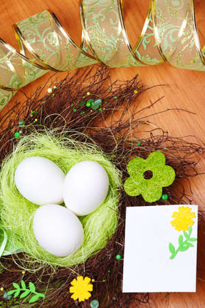 Nest with three eggs in it and blank greeting card beside photo
