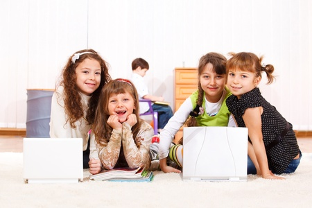 Group of cute smiling kids sit beside laptops photo