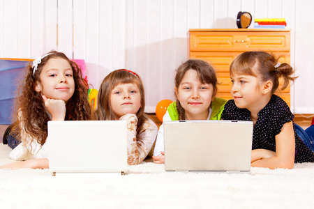 Four elementary aged girls lying in front of laptops photo