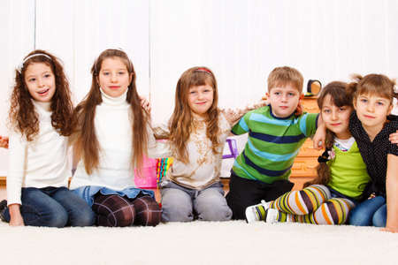 Six children sit in room, embracing photo