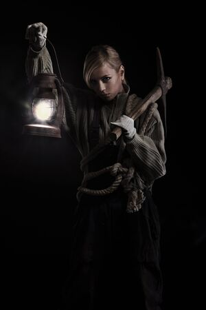 Woman holding heavy pick and oil lamp in hands photo