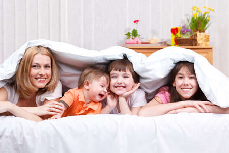 Happy family covered with blanket Stock Photo - 9060811