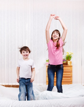 Two kids jumping on bed photo