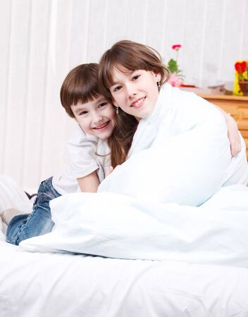 Brother and sister embracing on the bed Stock Photo - 9060846
