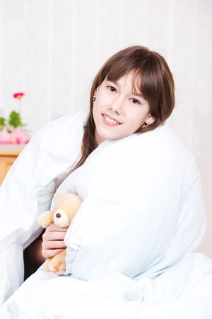 Smiling girl wrapping her body into blanket photo