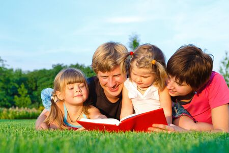offsprings: Parents reading book to their sweet offsprings Stock Photo