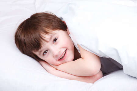 Cheerful kid lying in bed covered with blanket photo