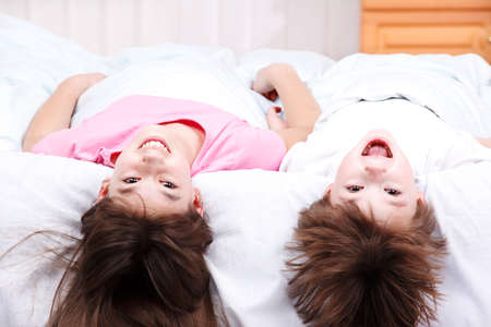 Boy and girl lying on bed with their heads upside down photo