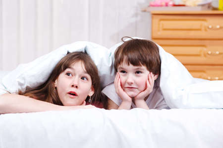 Two surprised children in bed photo
