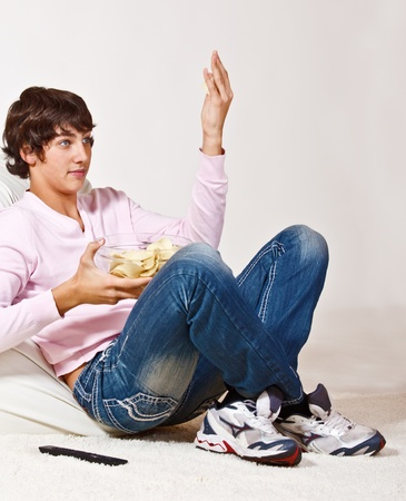Teenager with crisps in a bowl watching tv photo