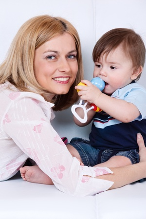 Portrait of a happy female and her toddler son playing with rattle photo