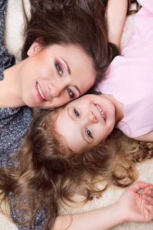 Portrait of mom and curly girl lying close to each other Stock Photo - 9191519