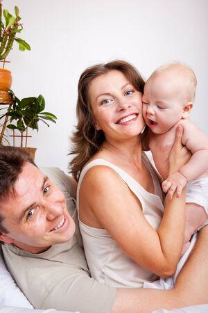 Les parents joviale et un bébé dans la chambre à coucher Banque d'images