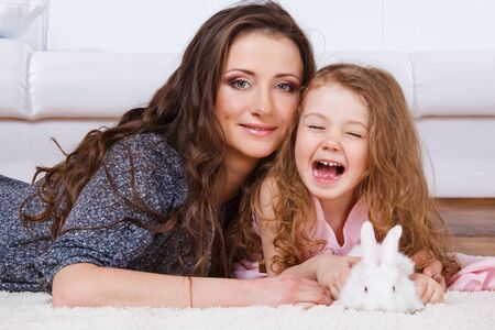 Laughing girl, her mother and  a white bunny lying  Stock Photo - 9191518