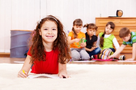 Cheerful curly girl laying on carpet with pencil photo