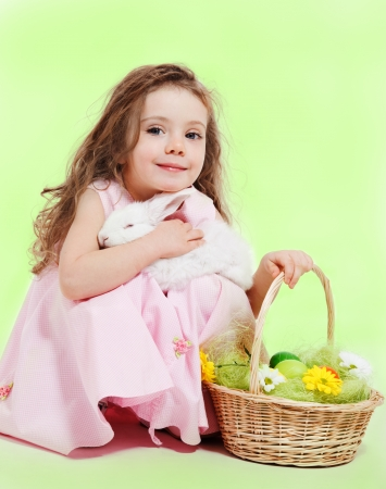 Curly little girl with Easter basket and white bunny in hands photo