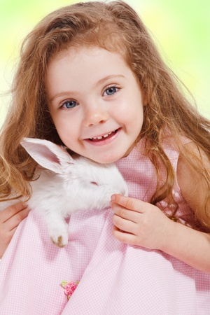 Portrait of a preschool girl holding white rabbit photo