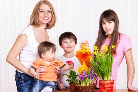Mother and children watering flowers photo