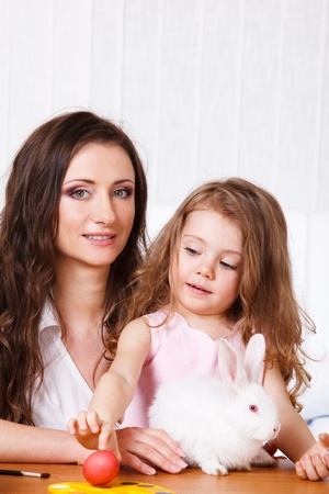 Mother and child with the Easter bunny and painted eggs photo