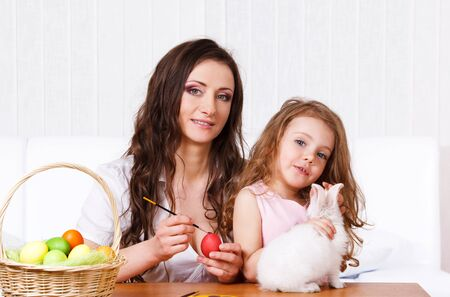 Mother painting eggs for the Easter party, girl playing with white rabbit Stock Photo - 9191543
