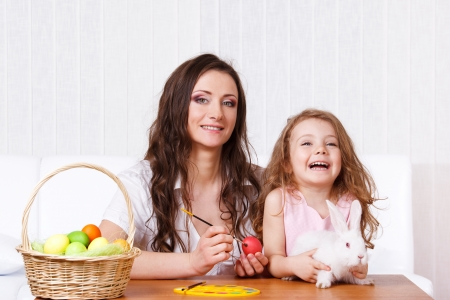 Happy mother and kid painting Easter eggs photo