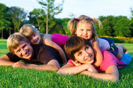 parents: Parents with little daughters  on the green grass Stock Photo