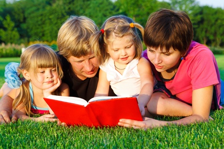 Sweet family reading a book on the green grass Stock Photo - 9191542