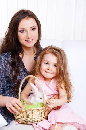 Mother and daughter sit on the sofa and holding basket with Easter bunny photo