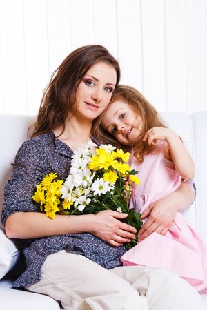 Curly kid and mother holding flowers photo