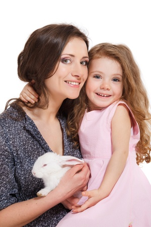 Laughing girl and mother holding white rabbit photo