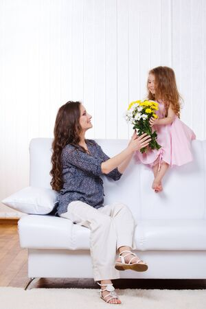 Girl presenting mother yellow and white flowers photo