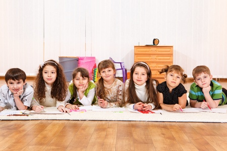 Group of seven junior school students lying in line  photo