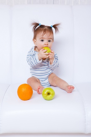 Angelic baby girl biting a green apple photo