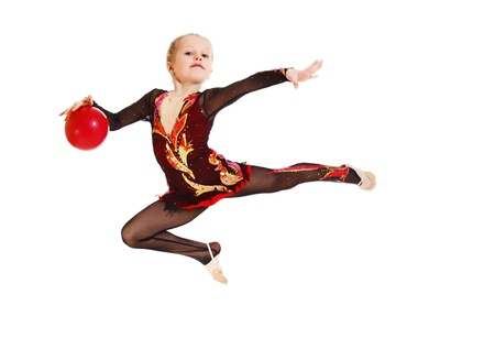 A sportive little girl jumping with a ball photo