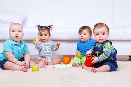Cuatro niños se sientan en la alfombra