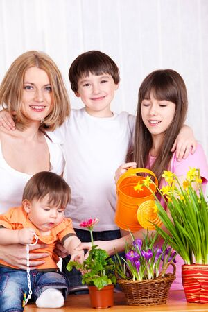 Cheerful and happy family watering flowers photo