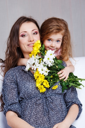 Sweet preschool girl embracing mom and presenting her flowers bunch photo