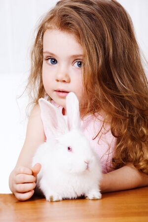 Portrait of a curly girl and white rabbit photo