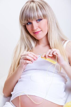 A blond pregnant woman knitting Stock Photo - 9330603