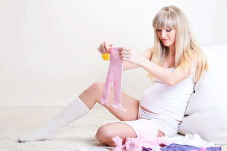 Pregnant young woman looking at baby  pink pants Stock Photo - 9330588