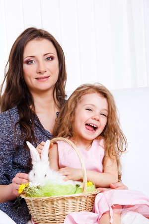 Mother and daughter with the Easter bunny in a wicker basket photo